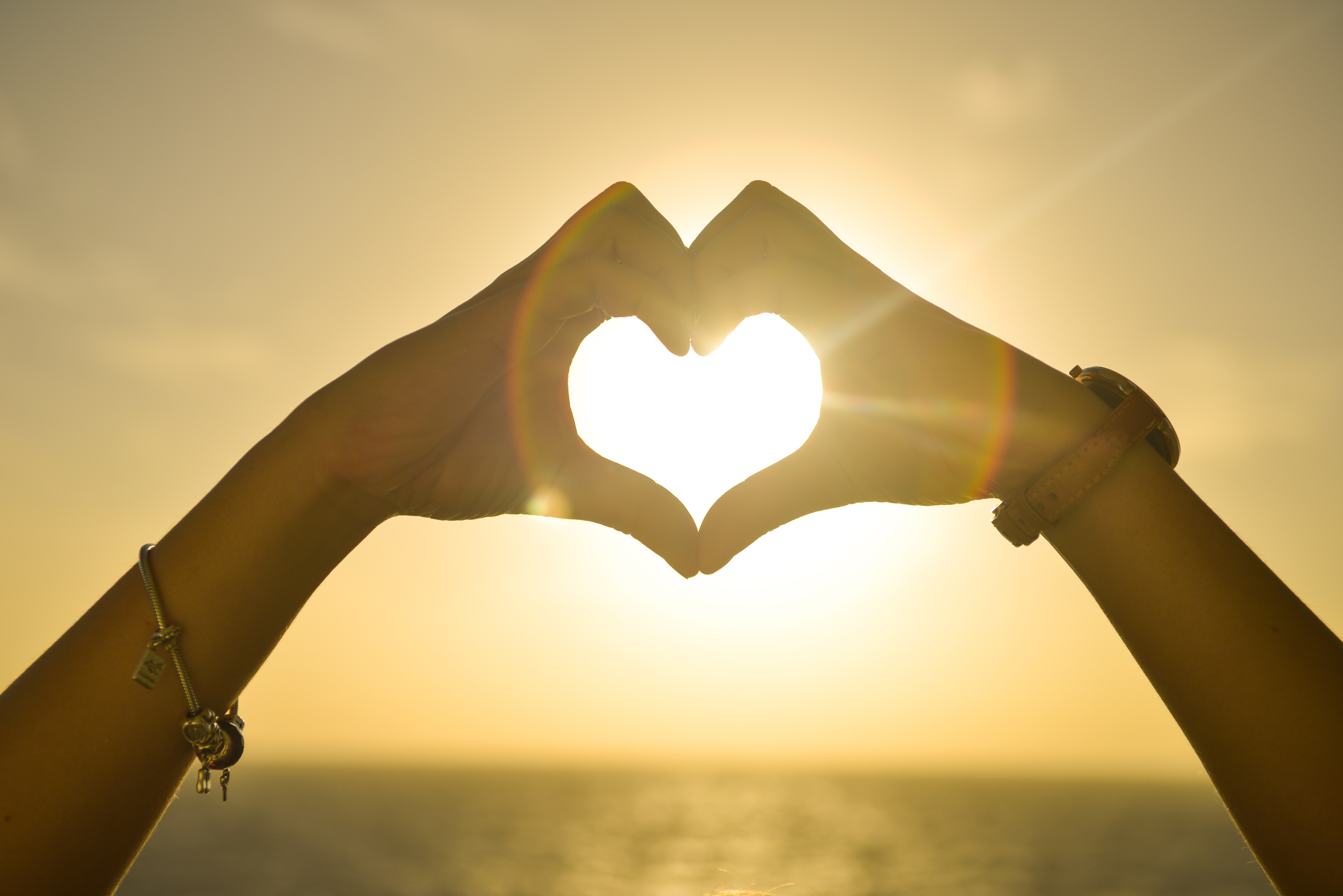 Canva - Two People Forming Heart Sign to Sun